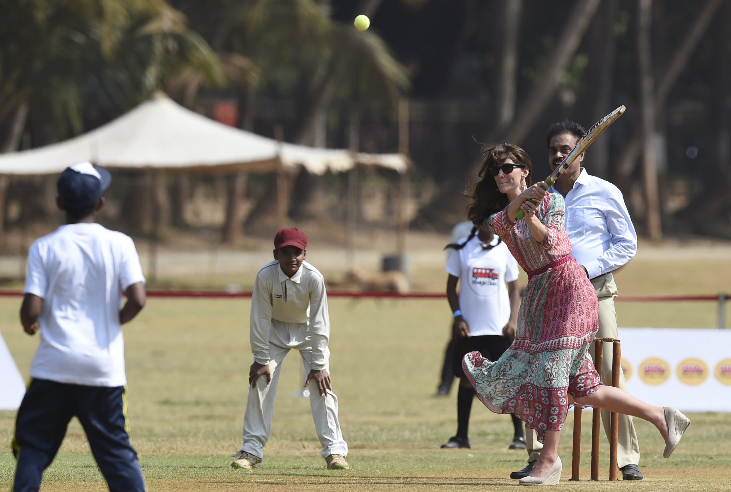 Catherine, Duchess of Cambridge (C), is watched by former Indian cricketer Dilip Vengsarkar (R) as she and Britain's Prince William play a game of cricket with Indian children, who are beneficiaries of NGOs, at the Oval Maidan in Mumbai April 10, 2016. REUTERS/Indranil Mukherjee/Pool