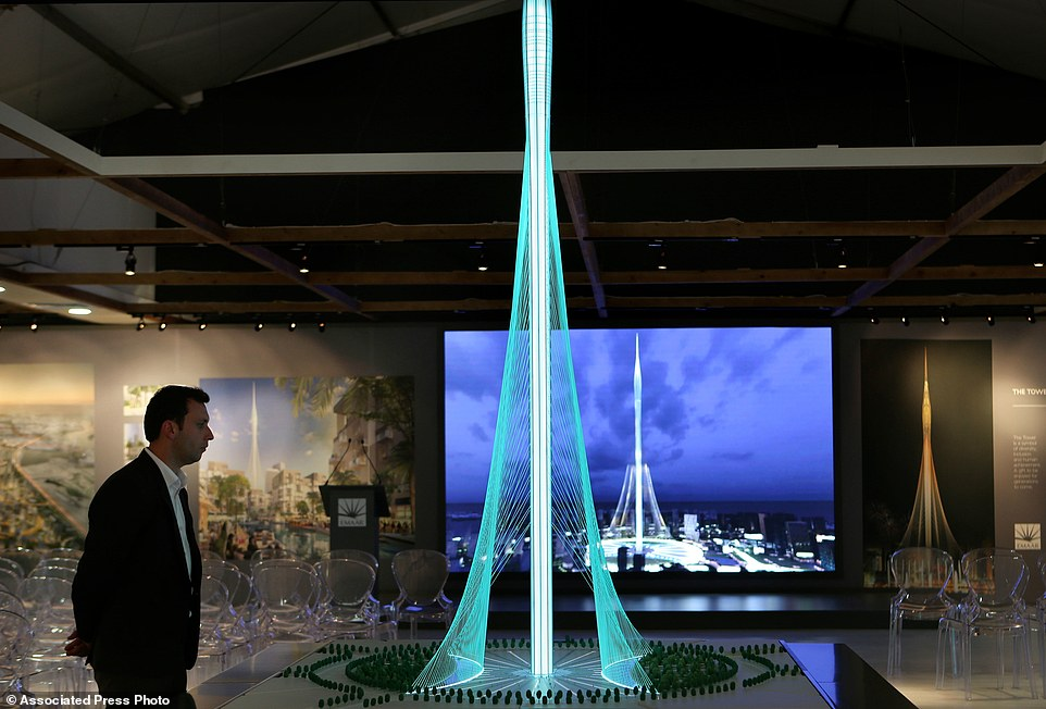 A man walks past a model of the Tower Project at Dubai Creek Harbour Development designed by Spanish-Swiss architect Santiago Calatrava Valls, in Dubai, United Arab Emirates, Sunday, April 10, 2016. Dubai is reaching for the sky once again, with the developer of its world's tallest building vowing Sunday to build an even taller tower bedecked with rotating balconies and elevated landscaping inspired by the mythical hanging gardens of Babylon. (AP Photo/Kamran Jebreili)